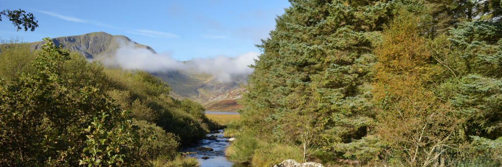 View down a valley in Snowdonia, low hanging clouds, a river and mountains in the distance. Peaceful